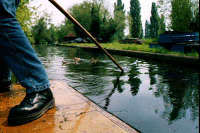 man standing on the back of a punt, pushing the pole into the river
