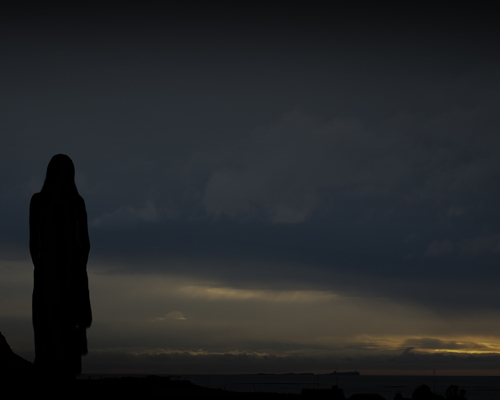 Dark image showing a woman silhouetted against a looming sky