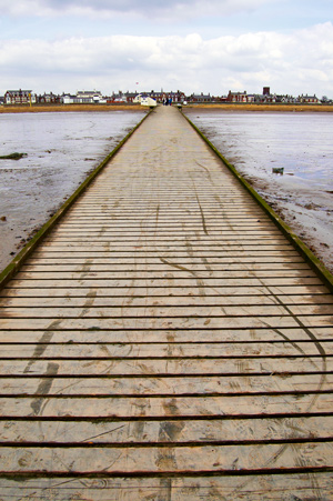a wooden path running through mud towards a town