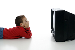 young boy lying on the floor watching TV